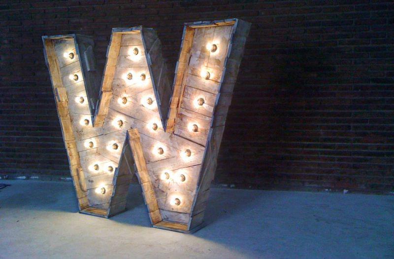 Letra W artesanal de madera envejecida escultura con iluminación bombillas identidad corporativa We Work