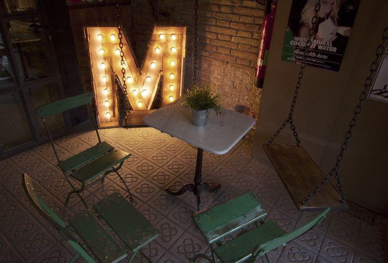 letra M del logo de madera iluminada con bombillas a medida para entrada restaurante Metric Market