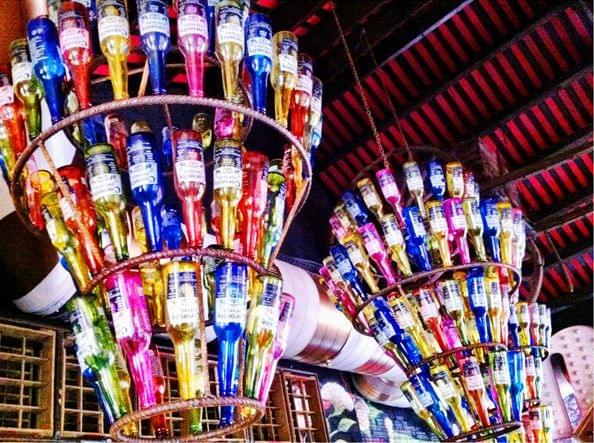 Lámpara de botellas de cristal con bombillas restaurante mexicano La Santa (Grupo Reini).